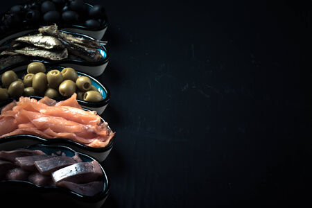assortment: Fish assortment and olives on a plate on a dark background. With space for text. tinted Stock Photo