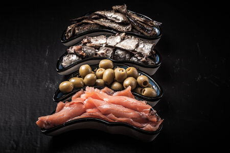assortment: Fish assortment and olives on a plate on a dark background. With space for text Stock Photo