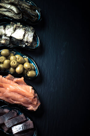 Fish assortment and olives on a plate on a dark background. With space for text. tinted Stock Photo
