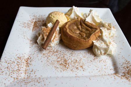 nata: Traditional Portuguese cake pasteis de nata  with ice cream, decorated with cinnamon and cocoa Stock Photo