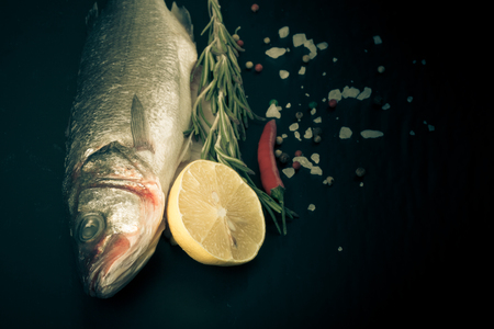 Fresh fish, lemon, pepper and rosemary on a black background. Tinted photo