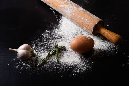 people eating restaurant: dough on a board with flour. eggs, rolling pin, garlic Stock Photo
