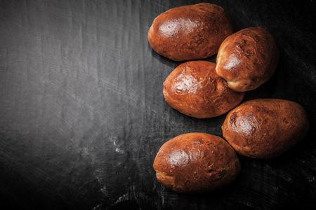 comiendo pan: empanadas con la carne o la col en un fondo negro.