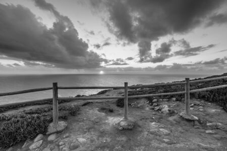 Wooden fence on the edge of Europe. Sunset. black and white photo