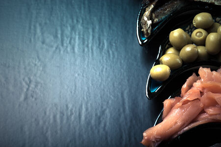 assortment: Fish assortment and olives on a plate on a dark background.