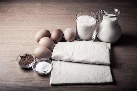 Milk, sugar, cocoa, puff dough, eggs and salt on a wooden board. Ingredients for pastry. Toned. photo