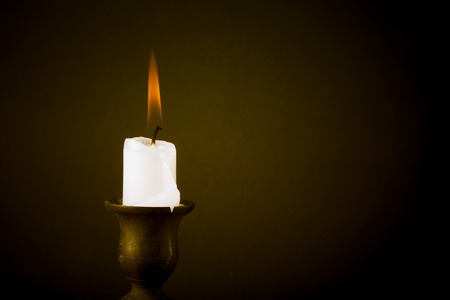 burning candle on a dark background. Tinted photo