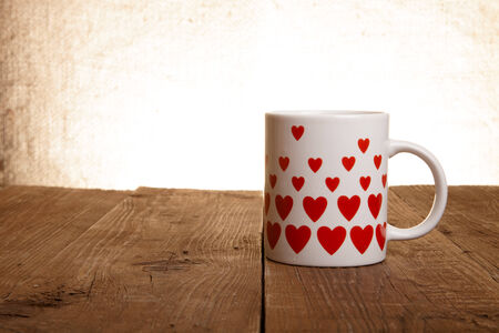 pictured: Mug with many pictured hearts on the old wooden table.