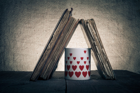 Old books and mug with many pictured hearts on the old wooden table. Toned. photo
