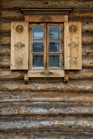 Windows with shutters, patterned on the wall of the old wooden house.