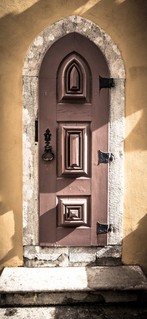 rustiness: Old wooden door with metal hinges and lock on the yellow wall. Toned. Stock Photo