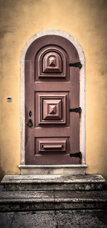 scraped: Old wooden door with metal hinges and lock on the yellow wall. Toned. Stock Photo