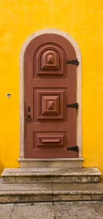 rustiness: Old wooden door with metal hinges and lock on the yellow wall.