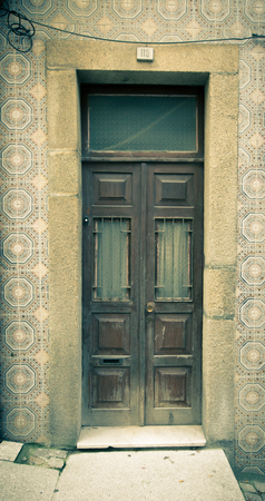 rustiness: Old wooden door with window on the wall with ceramic tile. Toned. Stock Photo
