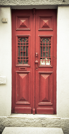 rustiness: Old red wooden door with window and grid. Toned.
