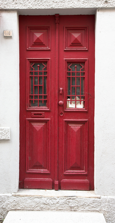 rustiness: Old red wooden door with window and grid.
