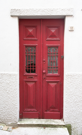 scraped: Old red wooden door with window and grid.