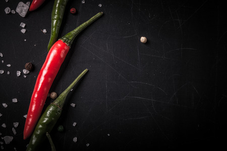 Red and green hot chilli pepper with sea salt and colored pepper on black background. Toned.
