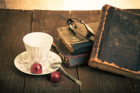Cup of coffee, shokolad, glasses and stack of old books on the old wooden table. Toned. photo