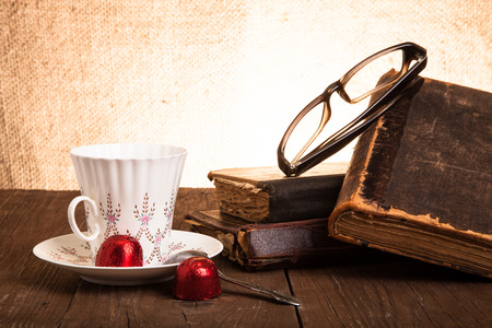 Cup of coffee, shokolad, glasses and stack of old books on the old wooden table. photo