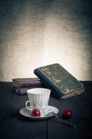 Cup of coffee, shokolad and stack of old books on the old wooden table. Toned. photo