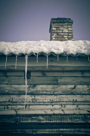Brick chimney on the snow-covered roof of a wooden house.  photo