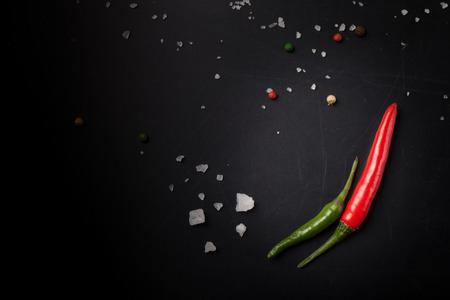 Rode en groene hot chili peper met zeezout en gekleurde peper op een zwarte achtergrond. Afgezwakt. Stockfoto