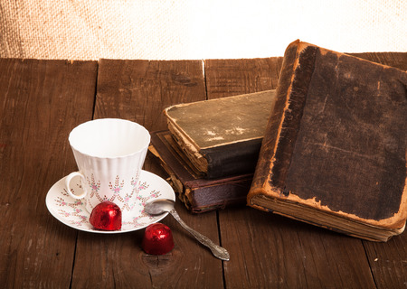 Cup of coffee, shokolad and stack of old books on the old wooden table. photo