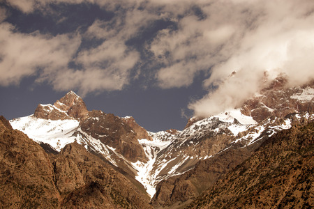 tajikistan: Clouds over the snow-covered tops of the rocks. Landscape. Toned.