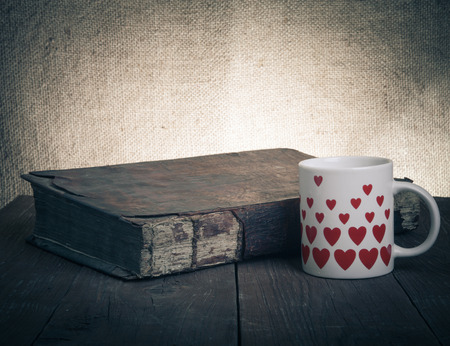 Cup of coffee, old books on the old wooden table. photo