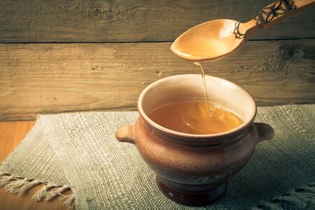 clay pot: Clay pot with ghee and spoon on linen napkin. Rustic still life. Wooden background. Toned.