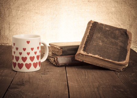 predecessor: old books and a cup with hearts on a wooden table