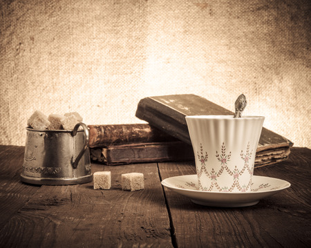Cup of coffee, sugar bowl and stack of old books on the old wooden table. photo