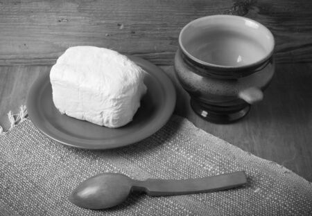 Butter on plate, clay pot and spoon on linen napkin. Rustic still life. Wooden background. Toned. photo