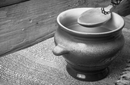 ghee: Clay pot with ghee and spoon on linen napkin. Rustic still life. Wooden background. Toned.