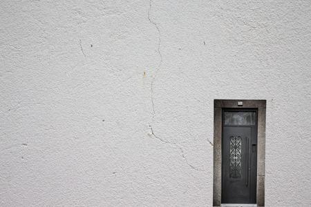 metall lamp: Retro metallic door on a light plastered wall.