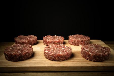 Ruwe kotelet van gehakt vlees op een houten snijplank op een zwarte achtergrond. Afgezwakt.