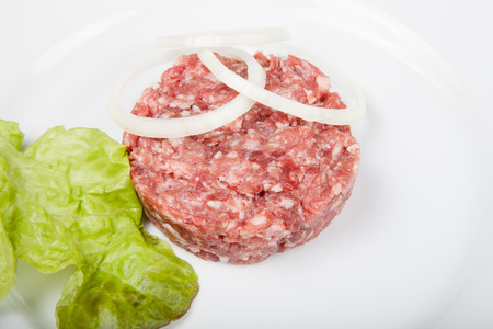 beefburger: Raw cutlet of minced meat with leaf of salad and rings of onion on a white plate.