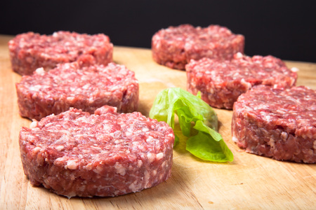 beefburger: Raw cutlet of minced meat on a wooden cutting board.