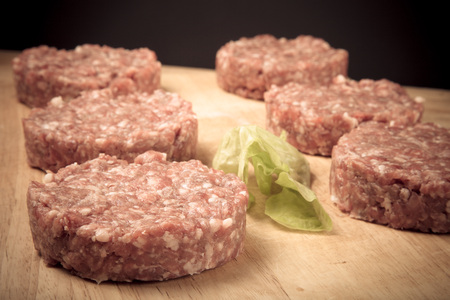 beefburger: Raw cutlet of minced meat on a wooden cutting board. Toned. Stock Photo