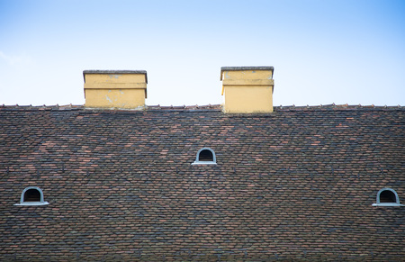 Old tiled roof with chimneys and dormers on blue sky background. photo
