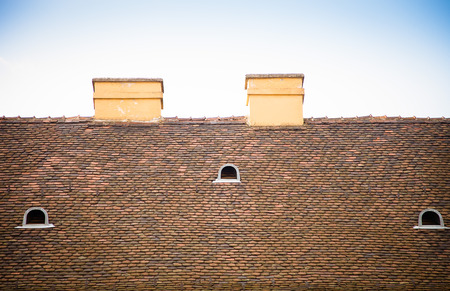 Old tiled roof with chimneys and dormers on blue sky background. Toned. photo