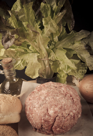 Meat ball, onion, herbs, olive oil and bread on a table. Ingredients for a hamburger. Toned. photo