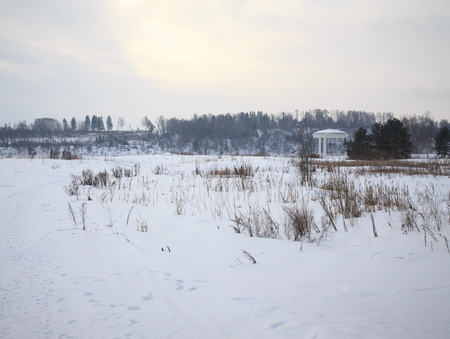 Winter snowy landscape. Gazebo on the background of forest and sky. photo