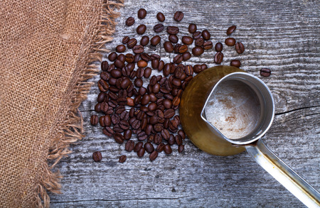 turk: Coffee turk and coffee beans on old gray wooden table with burlap. Stock Photo