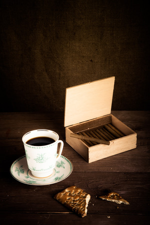 Cup of coffee, biscuits and a box of cigarettes on old wooden table. Toned Stock Photo