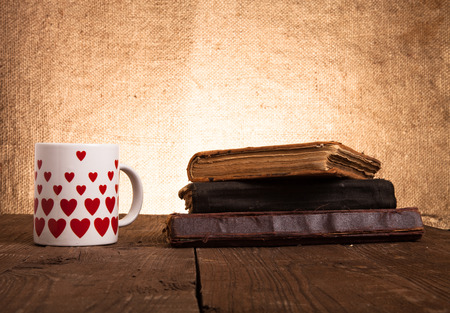 White mug with many pictured hearts and stack of old books on the old wooden table on burlap background. photo