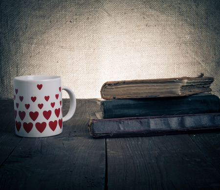 White mug with many pictured hearts and stack of old books on the old wooden table on burlap background. Toned. photo
