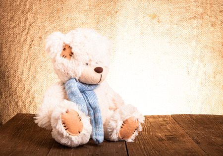 Teddy bear is sitting on the old wooden table. photo