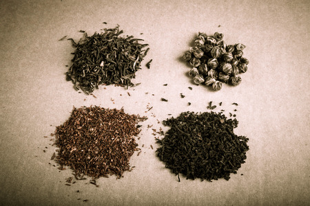 Four kinds of tea on a paper background. Toned. photo